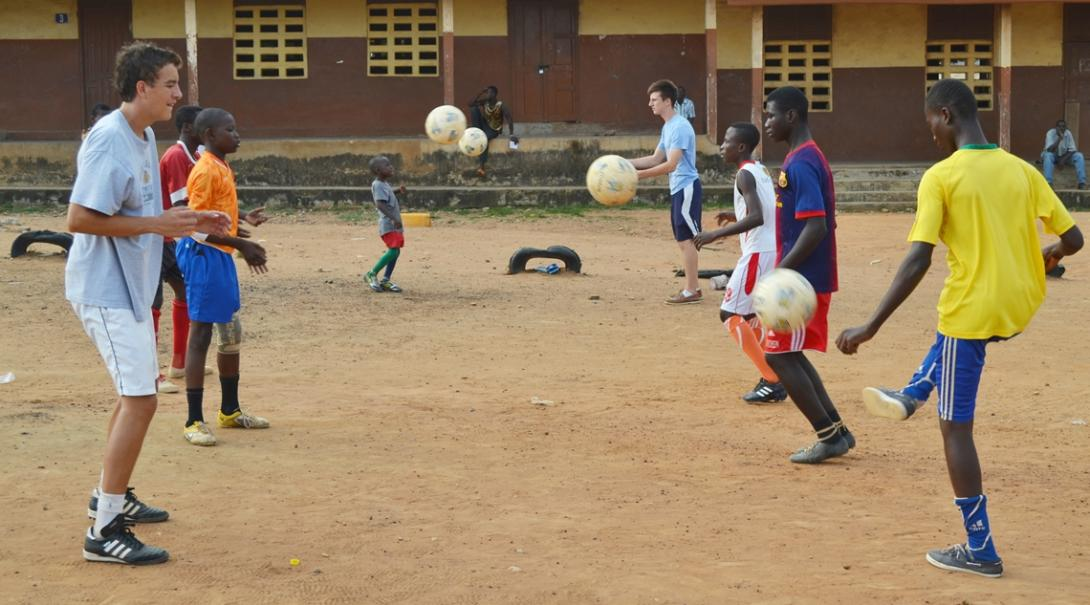ボールコントロールを教えるサッカーコーチボランティアとガーナの少年たち